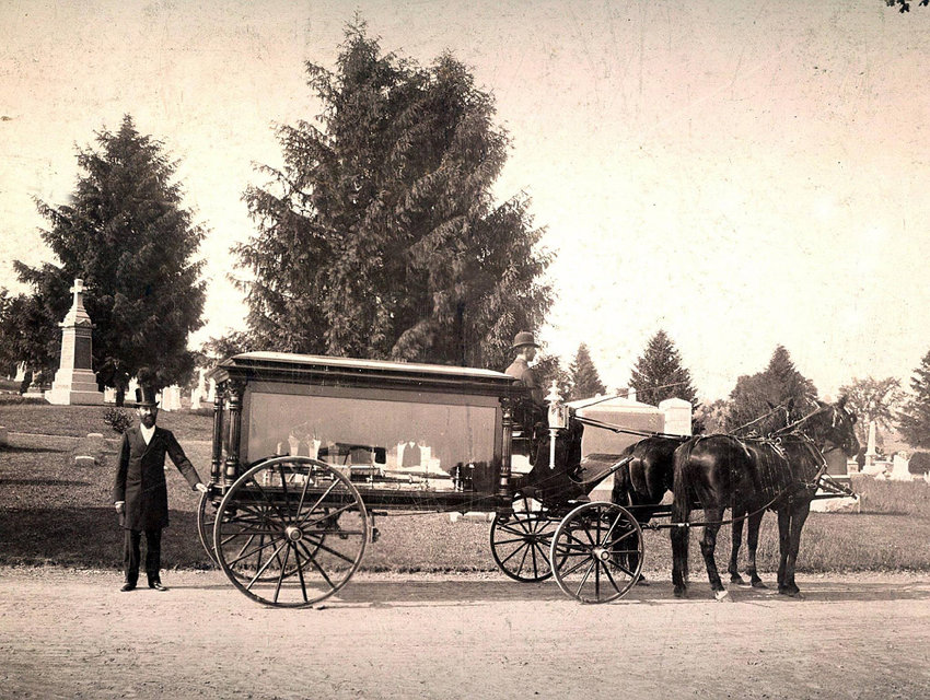 T.L. Millspaugh, founder of Millspaugh Funeral Directors, stands with a horse-drawn hearse in front of the Wallkill Valley Cemetery in Walden around the turn of the 20th Century