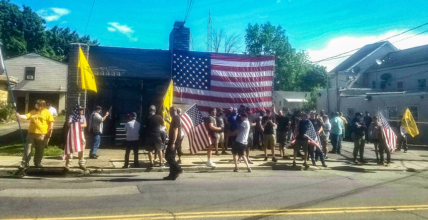 Protestors stand outside Casa di Dolore tattoo parlor and piercing shop as it opens in defiance of state's orders to remain shut down.