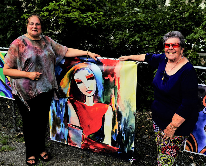 Gallery owner Elina Cordani [R] posed with one of her painting along with singer Angela Bruno at her outdoor concert.