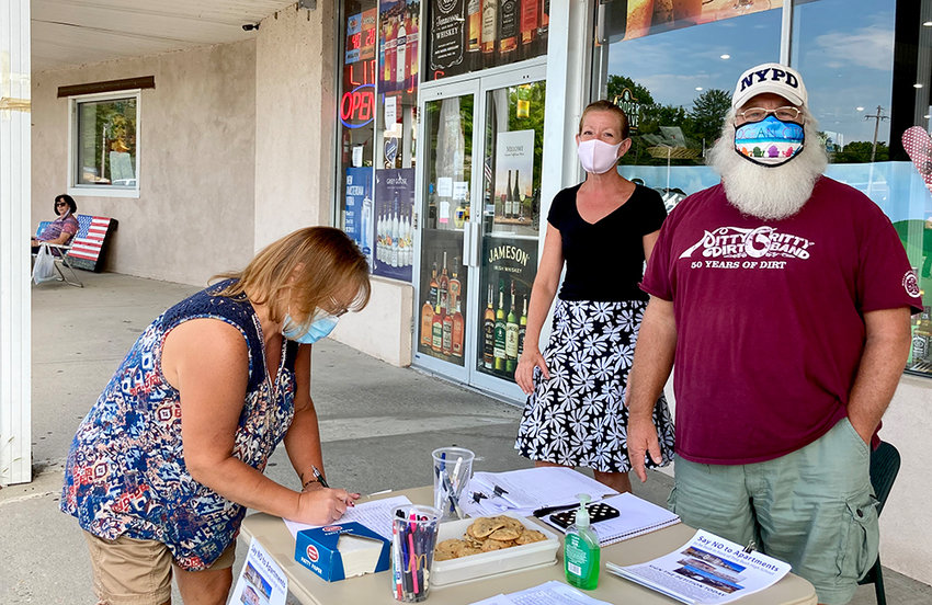 Kim Edgar signs the petition opposing proposed zoning changes in Crawford as Suzanne Schubert and Steve Decker meet with local residents.