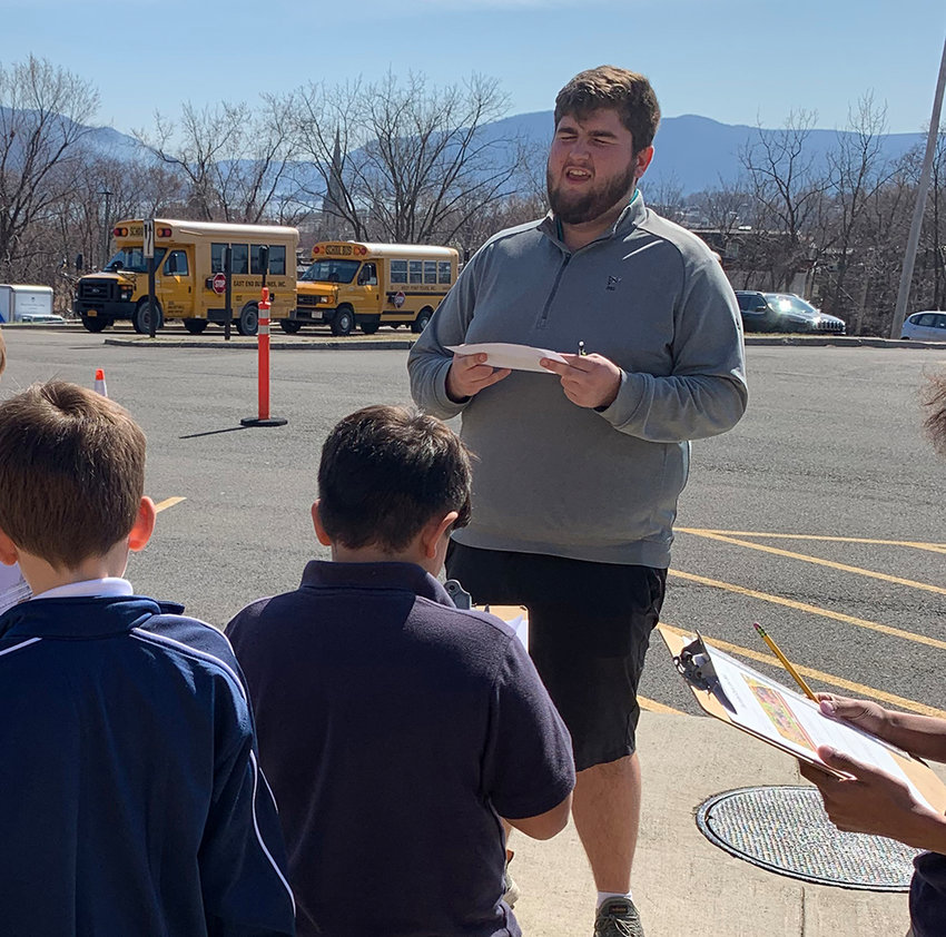 Charles Benfer of Milton,  (center), a Mount Mathematics major on the Education track, works with children at Bishop Dunn Memorial School on the Math Trails project. This photo was taken in March, before the COVID-19 pandemic required classes at the Mount and Bishop Dunn to transition online for the rest of the semester.