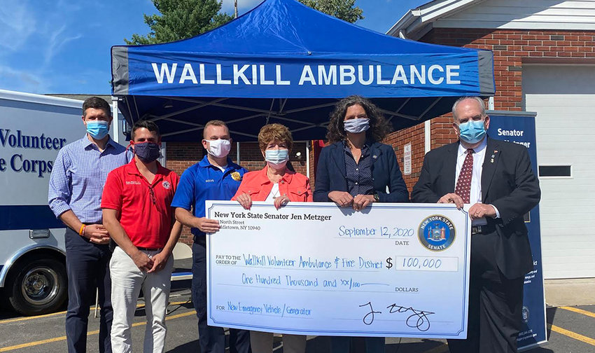 Government officials and Wallkill Volunteer Ambulance Corps and Fire District leaders pose with a $100,000 grant awarded to the ambulance corps and fire department. From left to right: Ulster County Executive Pat Ryan, Kenneth Ronk, director for the Hudson Valley Office of Minority Leader Brian Kolb, Wallkill Volunteer Ambulance Corps, Inc. Chief Doug R. Foster, Wallkill Fire District Commissioner Anne Barnhart, Sen. Jen Metzger and Wallkill Volunteer Ambulance Corps, Inc. Chairman of the Board and Treasurer, Douglas Foster, Jr.