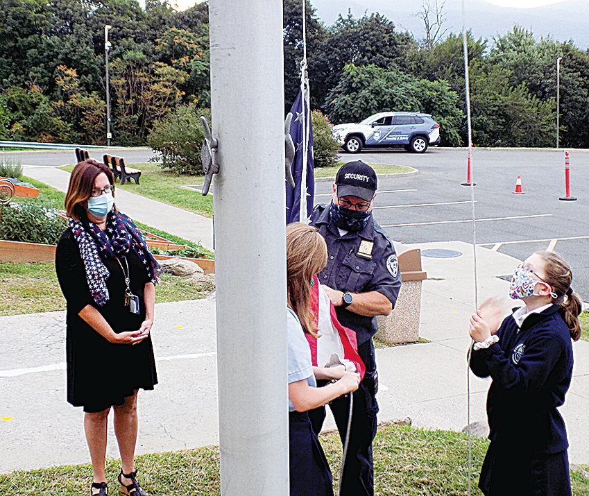 Frank White, Mount Saint Mary College security supervisor, helps Nancy Benfer, Principal of Bishop Dunn Memorial School, to raise the American flag on September 11, 2020.