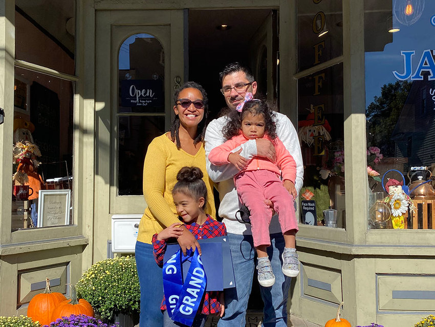 Java Blue Coffee & Food Market co-founders and co-owners Christina and Davide Porcu pose with their children Shila (plaid shirt) and Eden (pink shirt) after the ribbon cutting ceremony on Saturday.