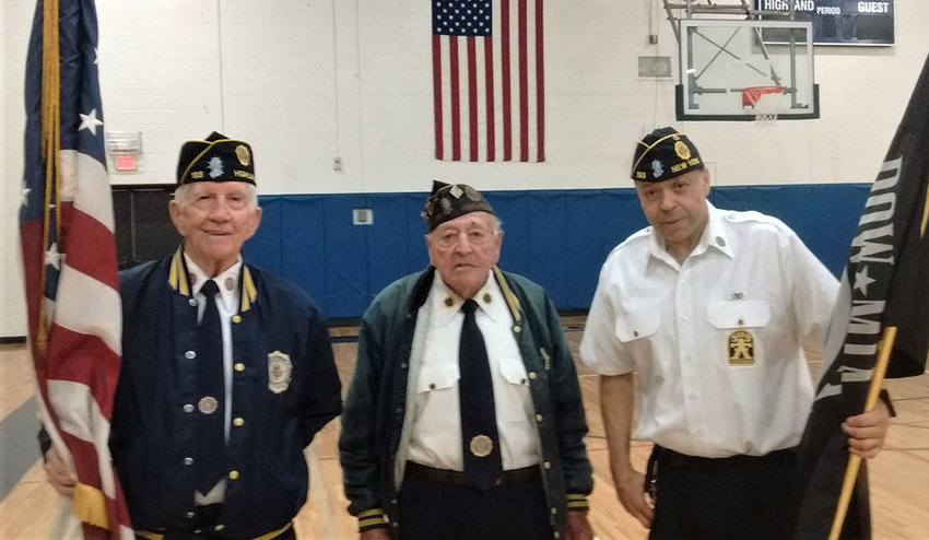 Commander Michael Schloemer [R] stands next to the late Chaplain Ben Bragg Sr. and Charlie Busick