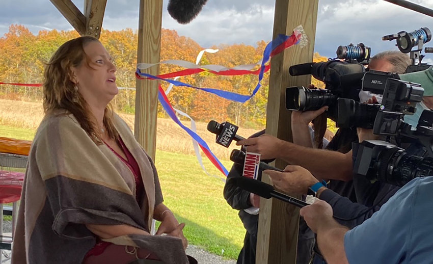 Maria Herb, a volunteer for the American Patriot Council, answers questions from the media on Saturday at the group's rally at Benedict Farm Park in the Town of Montgomery.