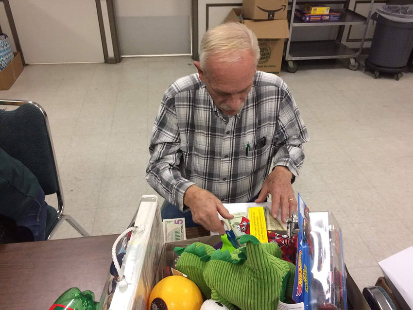Rev. Jim Van Houten helps prepare some gift packages at the Walden Fire House.