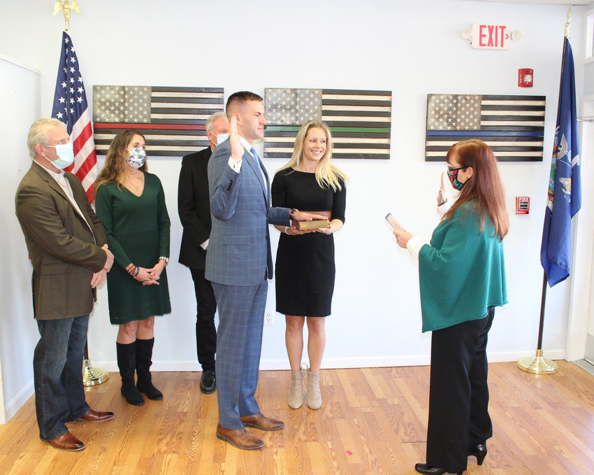 Assemblyman Colin Schmitt is administered the oath of Office by County Clerk Annie Rabbitt, Mrs. Nikki Schmitt holds the bible with family in the background.