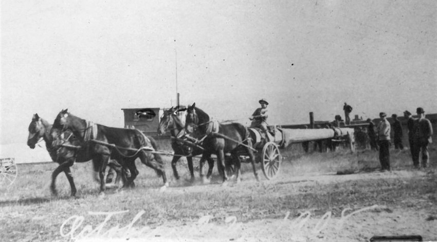 An archival photo, dated October 11, 1908, showing the first wooden flagpole being brought into Marlboro by a horse-drawn wagon.
