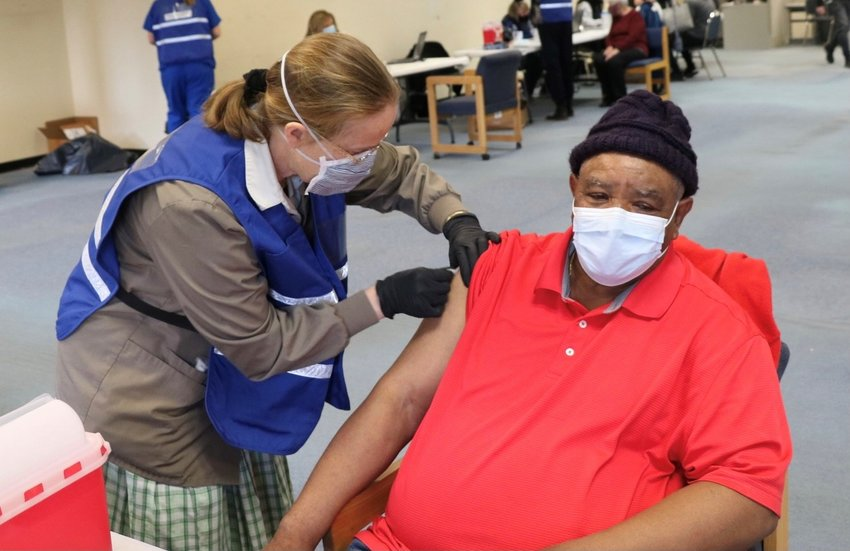 A volunteer nurse from the Bruderhof Community in Walden, administers a vaccination to Middletown's David Heath, 72