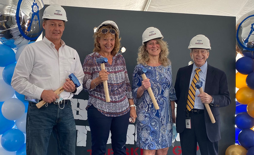 Members of the Pine Bush Central School District Board of Education as well as past and present district administrators pose for a photograph after breaking through the skills gap barrier with mallets. From left to right: Board Member Matthew Watkins, former Assistant Superintendent for Instruction Donna Geidel, Board President Gretchen Meier and Superintendent Tim Mains.