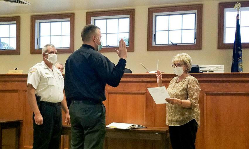 Daniel E. Montalto, one of two part-time police officers hired by the Town of Shawangunk on Thursday, is sworn in by Town Clerk Jane Rascoe, with Chief Gerald Marlatt (left).