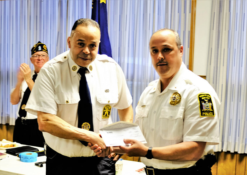 Lloyd Police Chief James Janso (r) presents a check for $1,250 to the American Legion Post Commander Michael Schloemer. The money was raised by a Lloyd Police Department fundraiser.