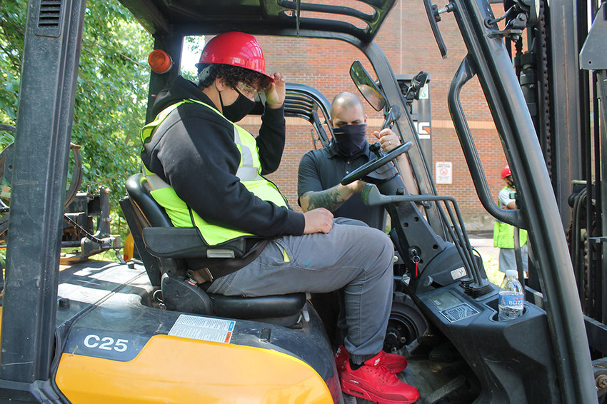 Ulster BOCES Motorcycle/Outdoor Power/Turf Management student Jordan Clarke (seated), from the Highland Central School District, practices operating a forklift under the guidance of Partner Rentals Logistics Manager Michael Pistone recently.