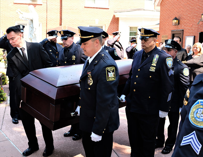 The casket of Paul Hansut is brought out from the church by (on right side) Chief James Janso (Lloyd Police Chief), Sgt. Paul Italiano (Brewster Police), K-9 Officer and Mike Barbagallo (City of Poughkeepsie Police). On far side, former Lloyd Police Chief Dan Waage, Capt. Rich Wilson (City of Poughkeepsie Police) and Detective Chris Libolt (City of Poughkeepsie Police).