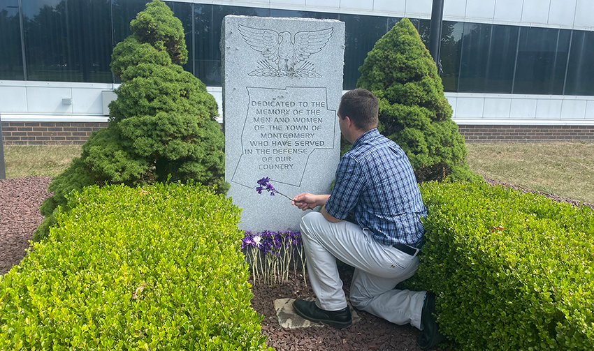 Montgomery Town Supervisor Brian Maher pays respects to the town's Purple Heart recipients at the veterans memorial at town hall.