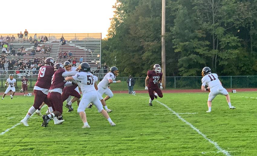 Highland quarterback Aden Wiser looks to elude a New Paltz defender.