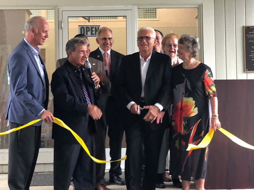 Doctor Rendano cuts the ribbon to mark the opening of the Rendano Building.