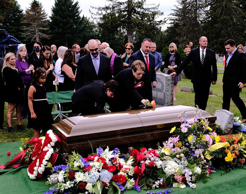 Kathleen Bragg placed a flower on her husband's coffin, bidding him a final farewell