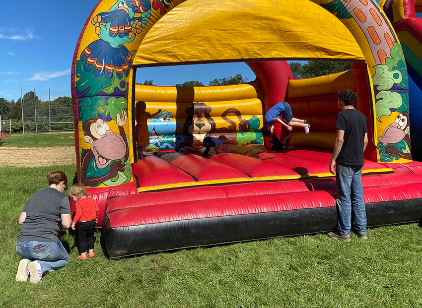 Children jump on the moon bounce at Saturday's Walden Harvest Fest.