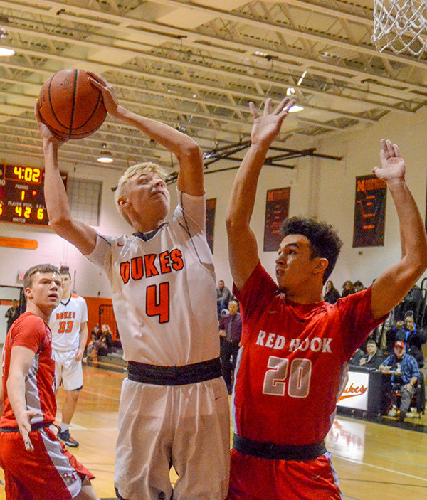 Marlboro's Daniel Rusk goes up for a shot as Red Hook's Reece Curley defends during Friday's Mid Hudson Athletic League boys' basketball game at Marlboro High School.