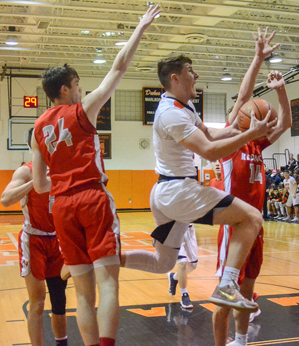 Marlboro's Sam Mongelli drives the lane as Red Hook's Jason Davis (24) and Dylan Bayliss defend during Friday's Mid Hudson Athletic League boys' basketball game at Marlboro High School.