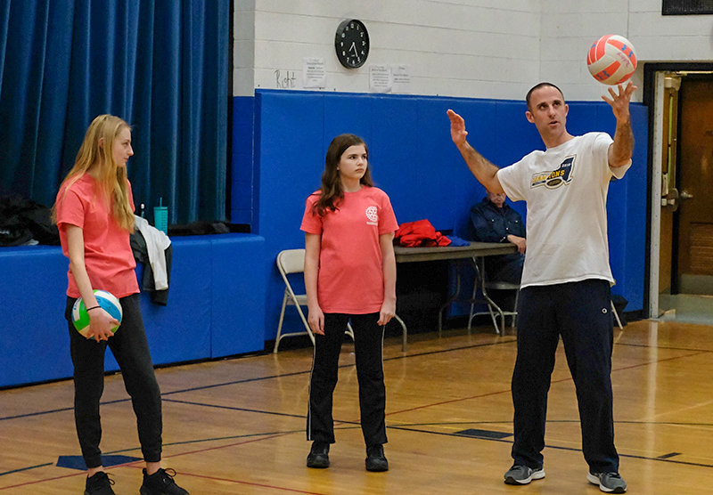 Coach Matt Giufre gives Sara Hoell (l) and Juli Hansen a few serving tips.