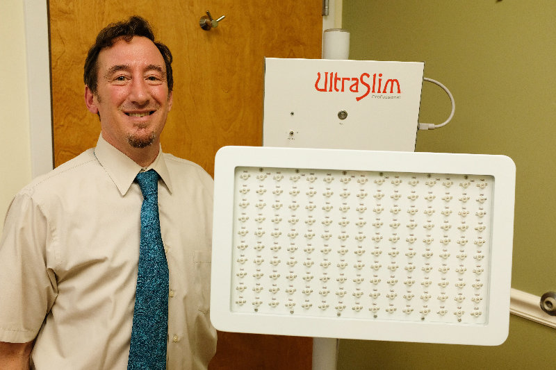 Dr. Stephen Weinman stands beside his new Ultra Slim machine that safely reduces fat in the body without surgery.
