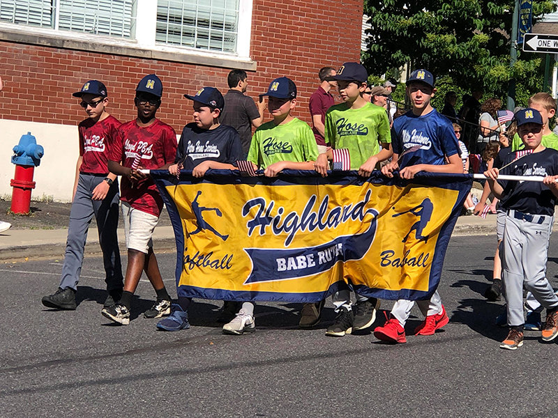 Highland Babe Ruth League baseball players marching.