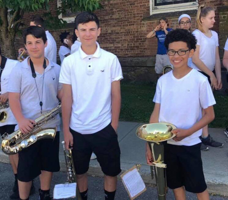 Middle School Marching Band Members Ben, James and Jaysean take a little break in the shade.
