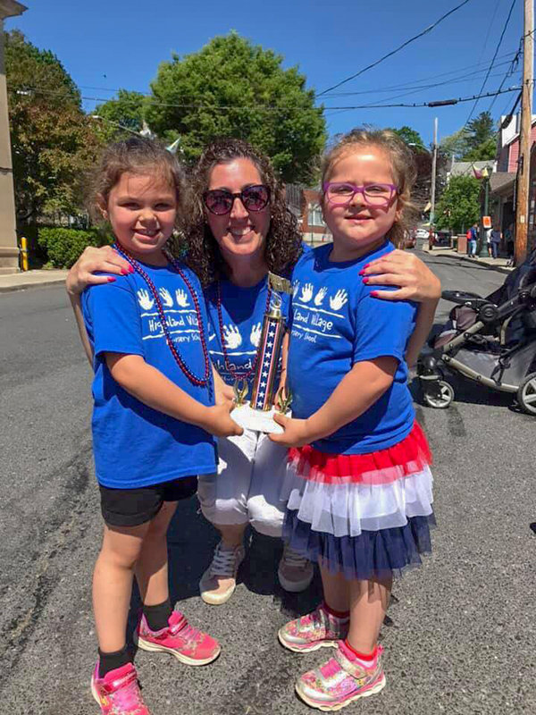Highland Village Nursery School Teacher, Amy Anthony and two students receive their 1st place trophy for Best Float.