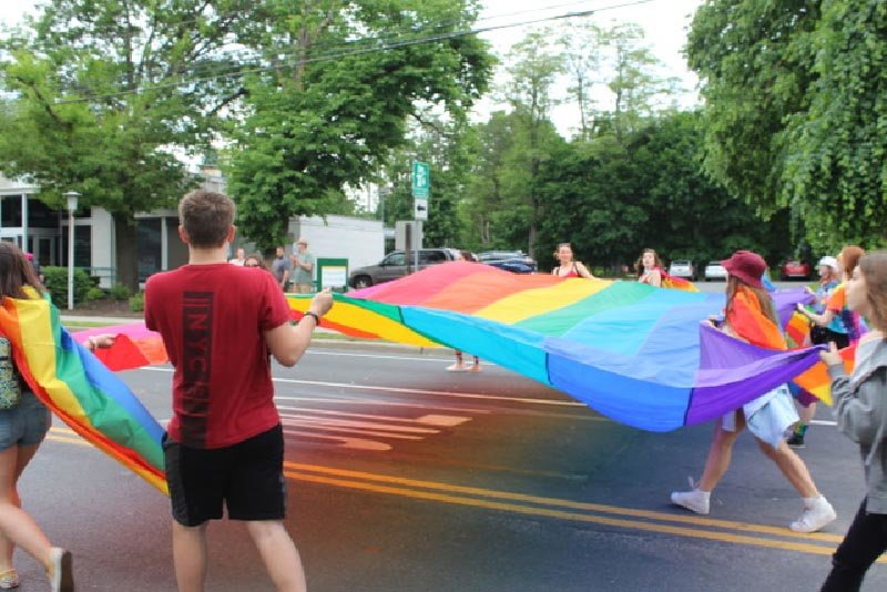 A huge rainbow flag is carried through the streets of New Paltz.