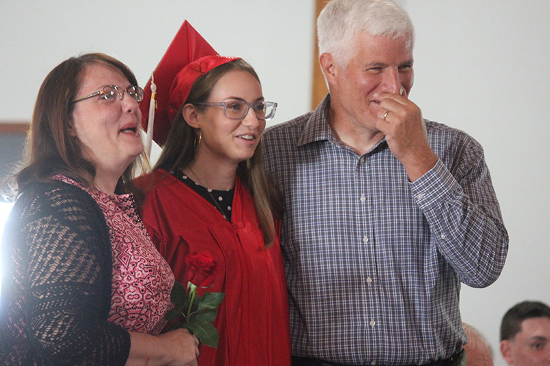 Jenna Angelo (center) with her parents as a fellow senior reads her letter.