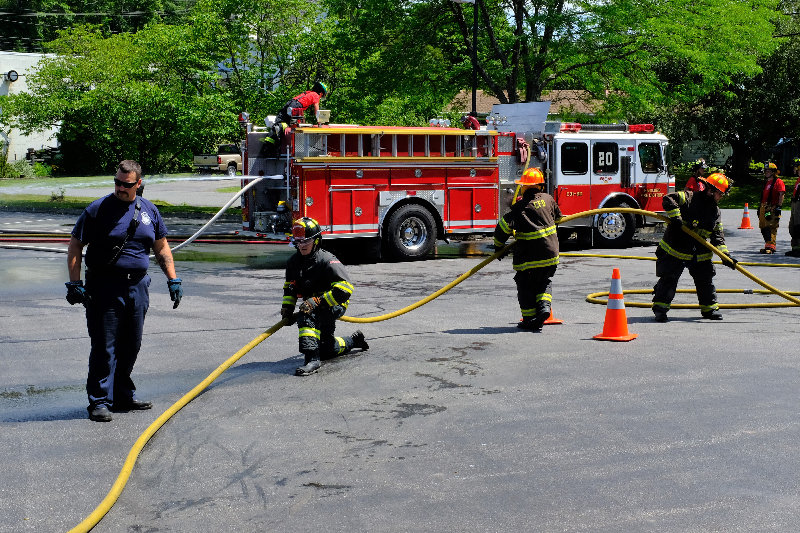 Instructor Will Farrell [l] teaches new firefighters how to properly advance a hose during a fire.