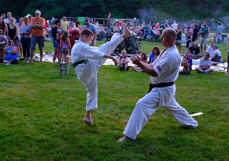 Green Belt Logan D'Anci [L] is performing an axe kick to split the wood held by Sempai Anthony Brooks.