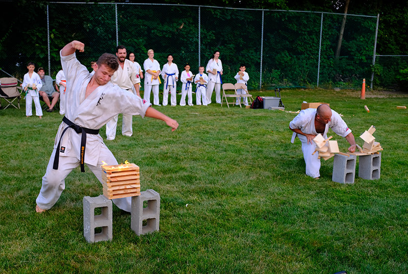 Sempai Sean King (l) punches through a firery stack of wood.