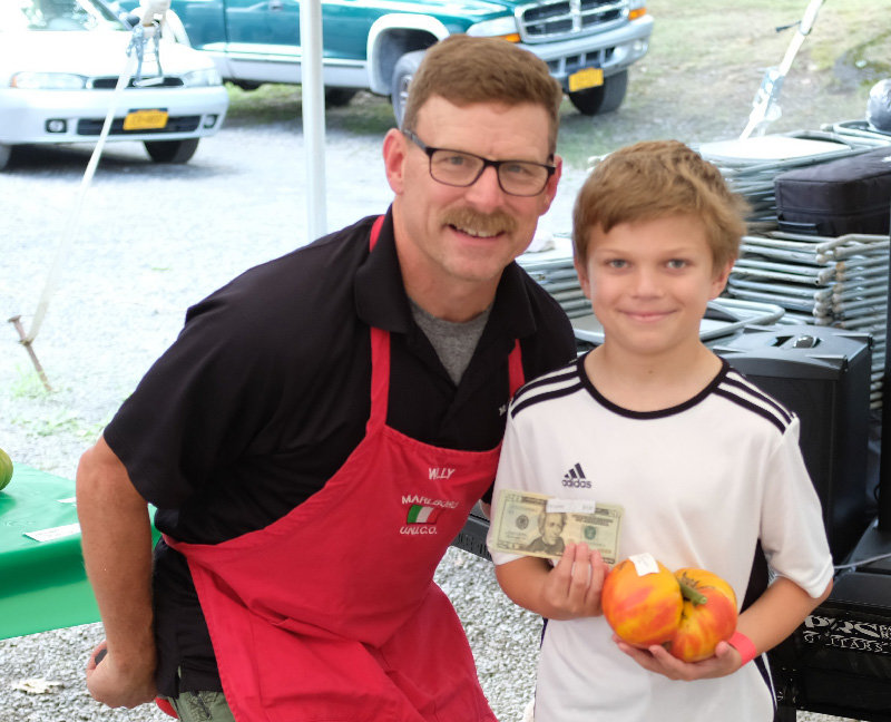 UNICO Master of Ceremonies Willy Biggin stands beside Devin McLaughlin who won in the under 16 category with a 999 gram tomato.