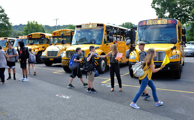Para-professional Christy DeNatale directs kids to their correct buses on the first day of school at the Middle School.