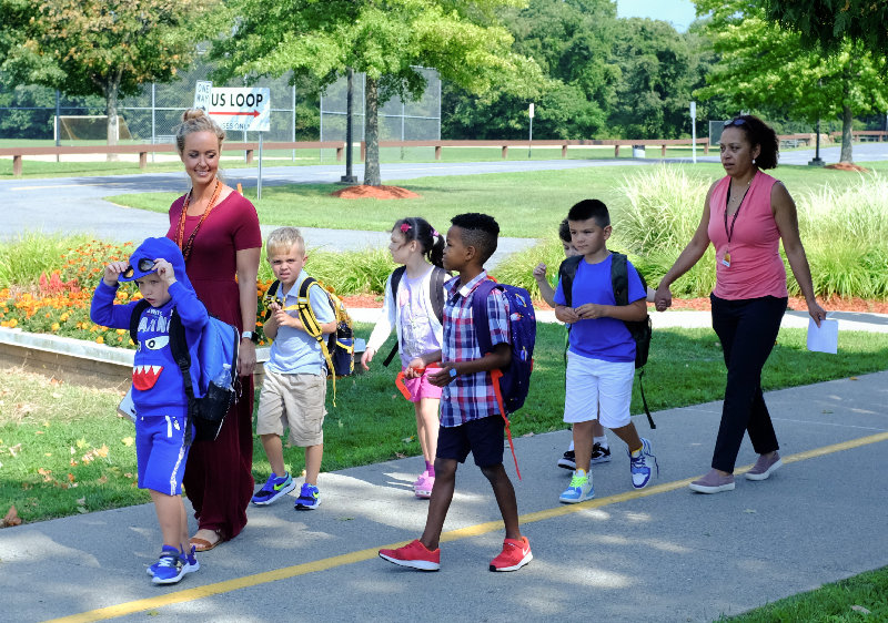 Teacher Nicole Ferrara (L) and para-professional Doris Garcia walk their students to the buses.