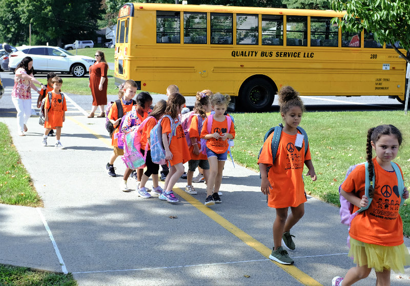 Teacher Noreen O'Keefe (L) helps kindergarten students to their buses.
