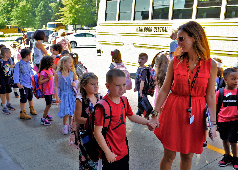 First Grade teacher Rebecca Auchmoody takes her class to their right bus.