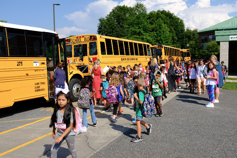 The buses are lined up at the Elementary School ready to take kids home.