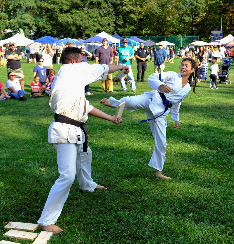 Blue Belt Leilani Cherry easily breaks a piece of wood with one kick that is held by Sensei Paradies.