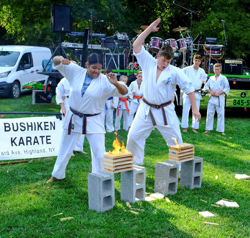 Kamily Figueroa (L) and Cain Osarczuk easily cut through several boards that are on fire at the karate demonstration.