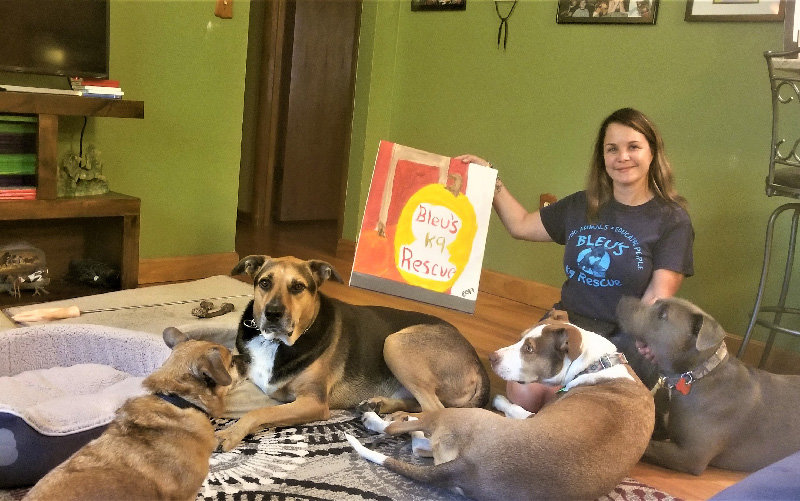 Diana Algarin poses with her four dogs and a sign that says Bleu's K9 Rescue.