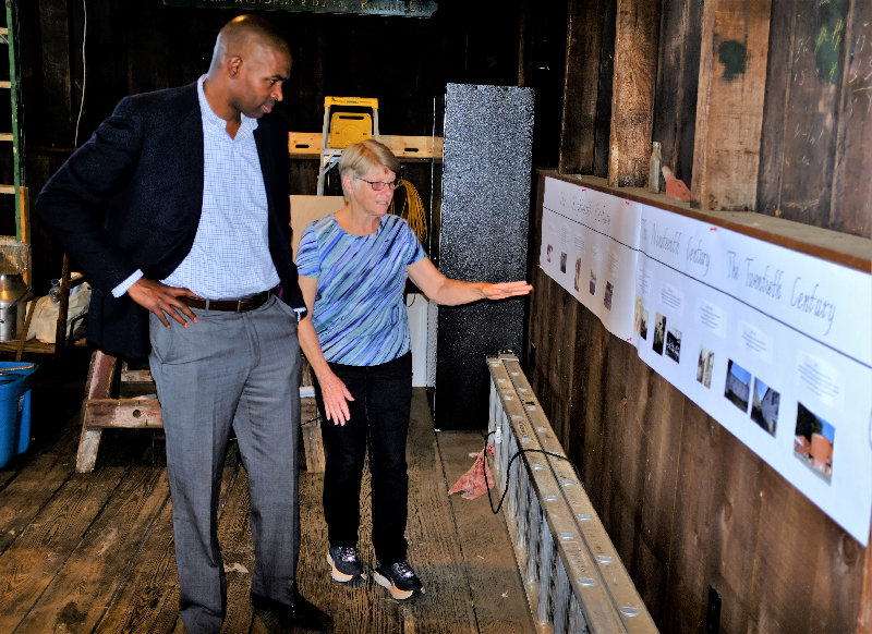 Judy Clarke, President of Meet Me in Marlborough, shows Congressman Delgado an evolutionary timeline of the Town of Marlborough.