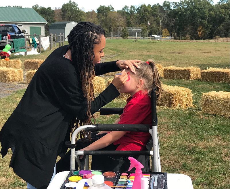 Avilda Whittmore paints Haley Meres' face.