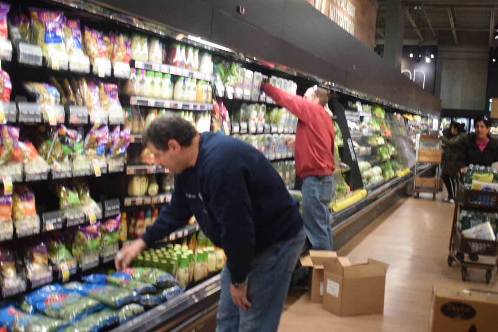 Volunteers from the Goodwill Fire Department helped re-stock the shelves at Market 32  Price Chopper on North Plank Road Friday night. The coronavirus outbreak led to school closures and shortages of many items on the shelves.