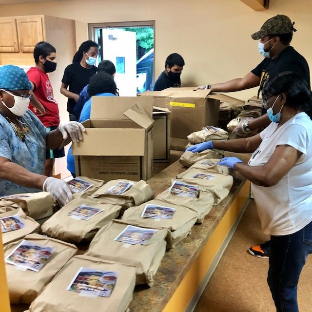 TRUSIC World Entertainment unpack meals prepared for Burton Towers residents on Saturday, June 27.