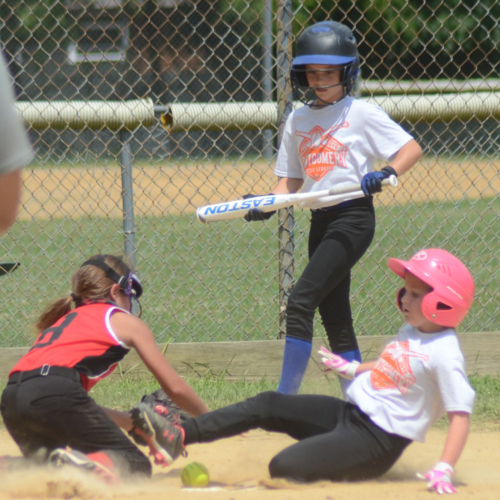 Montgomery's Hailey DeGroat slides into home plate as Pine Bush Falcon's pitcher Courtney Flynn tries to put down the tag during a Little League softball game at Veteran's Memorial Park in Montgomery on Saturday, Opening Day for Little Leagues throughout the area.